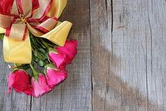 Vista superior del ramo de rosas rojas con la cinta en viejo fondo del tablero de madera Espacio correcto para el mensaje tarjeta Fotos de archivo libres de regalías