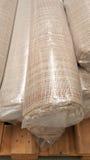 Vista superior del rollo marrón de la tela envuelto en bolso de rollo plástico en la acción de madera de la plataforma de la tela Fotos de archivo