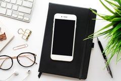 Vista superior del smartphone en la tabla del escritorio de oficina con los accesorios modernos Fotografía de archivo libre de regalías