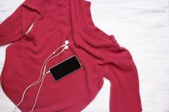Vista superior del suéter rosado de la mujer joven en el backgroun de madera blanco Foto de archivo