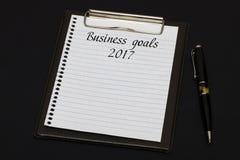 Vista superior del tablero y de la hoja blanca escritos con meta de negocio Fotos de archivo