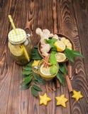 Vista superior del tarro de albañil con la bebida caliente en un fondo de madera oscuro Carambola, hojas, limón, jengibre, y cane Imagenes de archivo