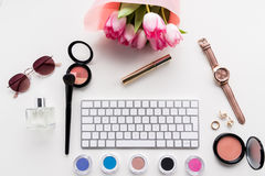 Vista superior del teclado de ordenador, de diversos cosméticos, de accesorios y del ramo de tulipanes rosados Fotos de archivo libres de regalías