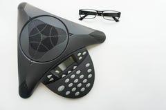 vista superior del teléfono de la conferencia del IP del voip con los vidrios del ojo en la mesa de reuniones Foto de archivo libre de regalías