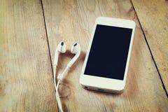 Vista superior del teléfono y de los auriculares elegantes blancos en la tabla de madera Fotos de archivo libres de regalías