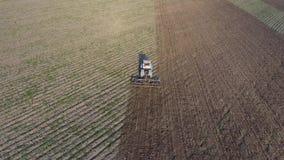 Vista superior del tractor que ara el campo disking el suelo Cultivo de suelo después de la cosecha almacen de video