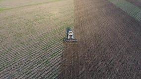 Vista superior del tractor que ara el campo disking el suelo Cultivo de suelo después de la cosecha metrajes