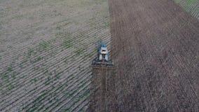 Vista superior del tractor que ara el campo disking el suelo Cultivo de suelo después de la cosecha almacen de metraje de vídeo