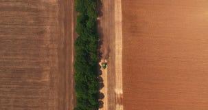 Vista superior del tractor que ara encima del campo después de recolectar en trigo metrajes