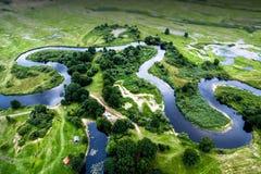 Vista superior del valle de un río de serpenteo entre campos verdes imagenes de archivo