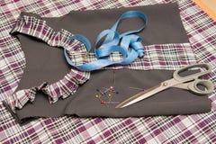 Vista superior del vestido de la escuela del billete del niño que miente en la tabla con los accesorios de costura Fotografía de archivo libre de regalías