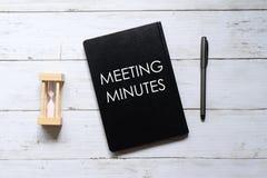 Vista superior del vidrio, de la pluma y del cuaderno de la hora escritos con ' REUNIÓN MINUTES' en el fondo de madera  fotografía de archivo libre de regalías