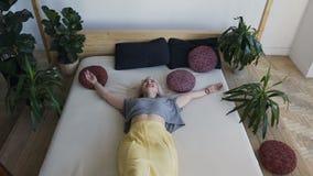 A vista superior, divertimento louro bonito encontra-se na cama grande e quebra-se seus braços Menina de sorriso em uma cama bran video estoque
