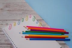 Vista superior do bloco de desenho aberto com copyspace da página vazia e de artigos de papelaria coloridos em uma mesa de madeir fotos de stock