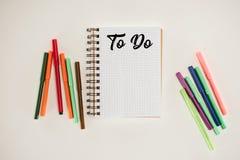 vista superior do bloco de notas com a placa para fazer a lista e marcadores coloridos Fotos de Stock