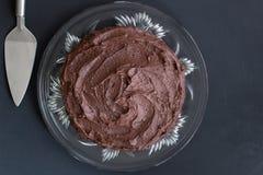 Vista superior do bolo de chocolate rico na placa de vidro com o servidor no bl Imagens de Stock