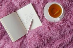 A vista superior do caderno e a palavra relaxam wtitting nele, pena, copo do chá no fundo cor-de-rosa fotografia de stock