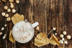 Vista superior do café quente do cacau com pipoca, folhas no w velho Fotos de Stock Royalty Free
