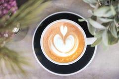 Vista superior do café quente do cappuccino no copo preto com arte do latte sobre foto de stock