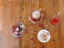 Vista superior do chá e das cookies Vela Scented e um copo do chá vermelho em um fundo de madeira Chaleira extravagante com chá d imagens de stock royalty free