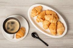 Vista superior do copo do café preto e de croissant frescos no po branco Foto de Stock Royalty Free