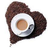 A vista superior do copo de café com coração deu forma a feijões Imagem de Stock