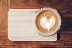 Vista superior do copo de café quente do cappuccino na bandeja de madeira com coração imagens de stock