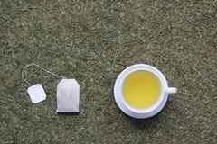 Vista superior do copo de chá com o saquinho de chá no fundo secado das folhas de chá foto de stock royalty free