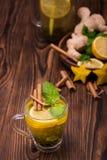 Vista superior do copo de chá da canela em um fundo de madeira escuro A sweet tea cup with carambola, cut lemon, mint leaves and  imagem de stock