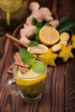Vista superior do copo de chá da canela em um fundo de madeira escuro A sweet tea cup with carambola, cut lemon, mint leaves and  imagem de stock royalty free