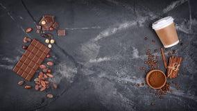 Vista superior do copo para viagem descartável do modelo com especiarias e barras de chocolate com feijões e avelã de cacau imagens de stock