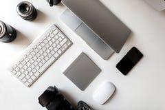 Vista superior do desktop branco em que se encontram as lentes profissionais à câmera, portátil, teclado, telefone, rato sem fio fotografia de stock
