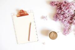 Vista superior do desktop do trabalhador fêmea com prancheta, flores e artigos diferentes dos materiais de escritório Espaço de t Imagem de Stock