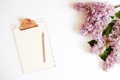 Vista superior do desktop do trabalhador fêmea com prancheta, flores e artigos diferentes dos materiais de escritório Espaço de t Fotografia de Stock Royalty Free