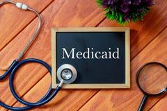 Vista superior do estetoscópio, da lupa, da planta e do quadro-negro escritos com Medicaid no fundo de madeira Conceito da saúde fotos de stock