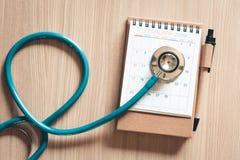 Vista superior do estetoscópio no calendário para o conceito do controle de saúde , Nomeação anual do doutor para o controle físi fotografia de stock