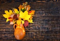 Vista superior do jarro bonito da argila com folhas e trigo de outono na Imagem de Stock Royalty Free