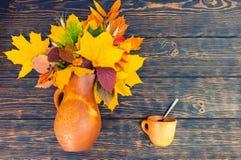 Vista superior do jarro bonito da argila com folhas e trigo de outono próximo Foto de Stock Royalty Free
