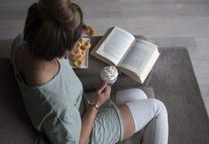 Vista superior do livro de leitura da mulher em casa no sofá com leite de chocolate e as cookies quentes fotos de stock royalty free