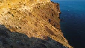 Vista superior do penhasco litoral com o mar azul no por do sol tiro Ideia bonita da luz dourada do por do sol em penhascos rocho vídeos de arquivo