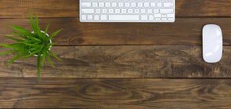 A vista superior do plano largo coloca a tabela da madeira do local de trabalho do escritório fotos de stock