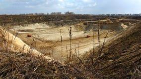 Vista superior do poço de argila do ar livre com as máquinas escavadoras da mineração sob o céu azul Fotografia de Stock Royalty Free