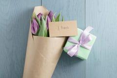Vista superior do presente com as tulipas roxas no papel do ofício no fundo de madeira azul com cartão do 8 de março Fotos de Stock