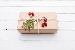Vista superior do presente do Natal envolvida no ofício e decorada com várias coisas naturais na madeira branca Foto de Stock