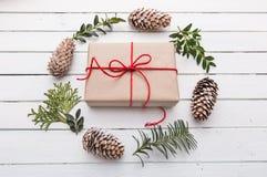 Vista superior do presente do Natal envolvida no ofício e decorada com várias coisas naturais na madeira branca imagens de stock