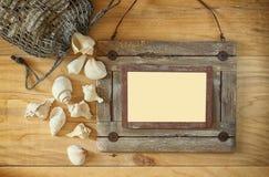 Vista superior do quadro de madeira náutico velho e de conchas do mar naturais na tabela de madeira Fotografia de Stock Royalty Free