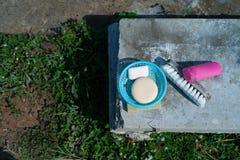 Vista superior do sabão na cesta plástica e da escova para a lavanderia com a garrafa plástica do champô posta sobre o assoalho c imagem de stock royalty free