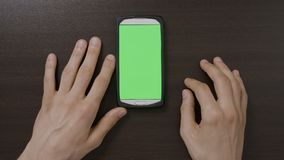 Vista superior do smartphone novo dos testes do homem de negócio com aplicações swiping chaves zumbir e consultar do croma na mes filme