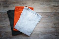 Vista superior do t-shirt da cor na prancha de madeira cinzenta Imagens de Stock