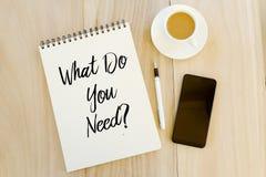 Vista superior do telefone celular, da pena, de uma xícara de café, e do caderno escrito com pergunta o que você precisam? Concei imagens de stock royalty free